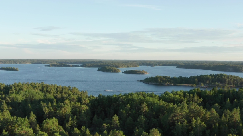 Swedish archipelago in aerial drone shot flying over forest and islands. Swedens most beautiful nature overview shot. Trees and green woods on warm summer evening close to Stockholm city   Shutterstock HD Video #1060777525