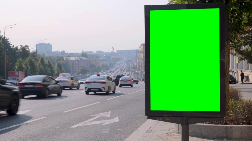 Green screen billboard located on a busy street. Cars move in a stream. Working day morning. In the foreground there is an arrow indicating the direction of the vehicles.   Shutterstock HD Video #1060794391