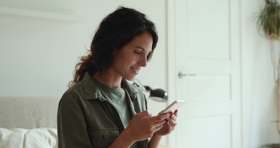 Pretty woman sit on couch in living room holding smart phone, chatting use social media network, watch received video from friend, choose goods on internet having fun with modern wireless technology Royalty-Free Stock Footage #1060801249