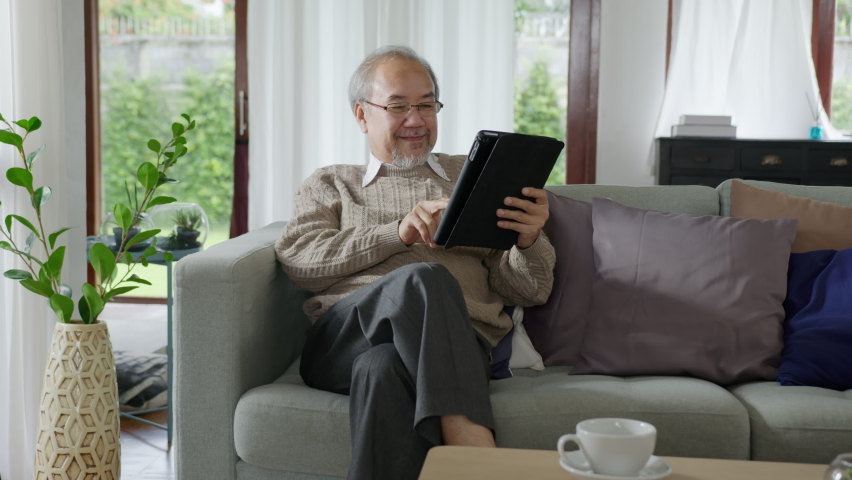 Candid of old asian retired man using tablet computer to transfer money online or financial payment and read text, smile or laugh with happy and positive. Senior asian with digital technology concept Royalty-Free Stock Footage #1060802854