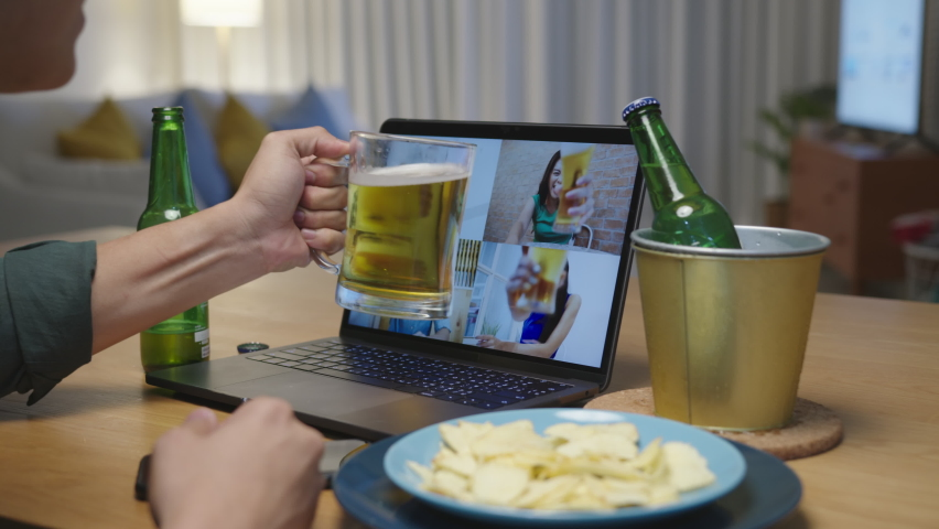 Close up : Attractive young happy asian man enjoy relax night party event online celebration festive with friends at home clinking beer with glass and bottle toasting drinking via video call.