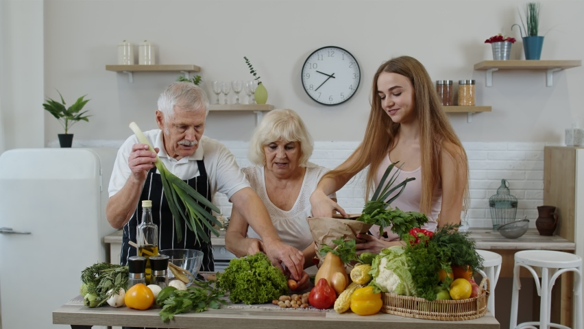 Senior couple in kitchen. Grandparents receiving vegetables from granddaughter. Listening advices of healthy food nutrition. Raw food eating diet. Joyful elderly lifestyle, World vegan day concept