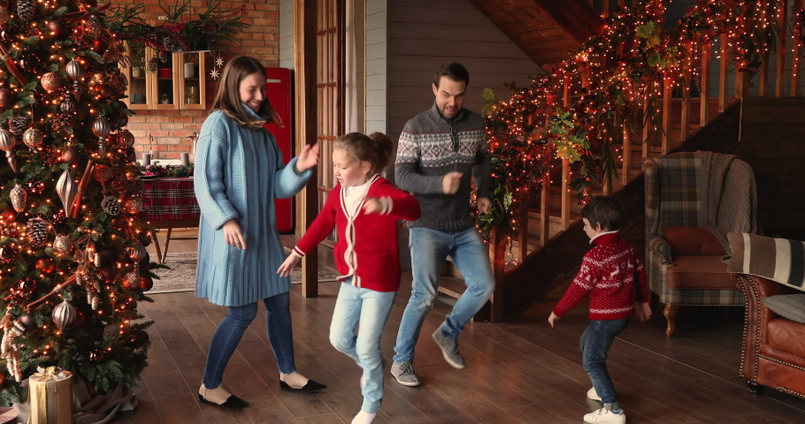 Full length happy family with little children celebrate Christmas Eve festive time listen funky music dancing at beautifully decorated twinkle lights and xmas tree house. Holiday mood, hobby concept Royalty-Free Stock Footage #1060811299