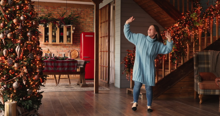 Carefree vivacious woman funny housewife sing song dancing in decorated illuminated twinkle lights glowing xmas tree house hall on Christmas Eve. Female celebrate New Year feel alive and happy concept Royalty-Free Stock Footage #1060811302