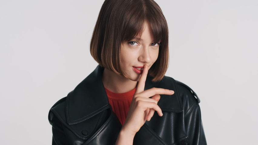 Beautiful stylish brunette girl with bob hair has intriguing look asking to keep secret isolated on white background. Shh expression | Shutterstock HD Video #1060811617