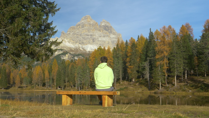LOW ANGLE, COPY SPACE: Unrecognizable young man sits on an empty wooden bench and observes the breathtaking fall colored mountain and lake landscape. Hiker enjoying the scenic views of lake Antorno.