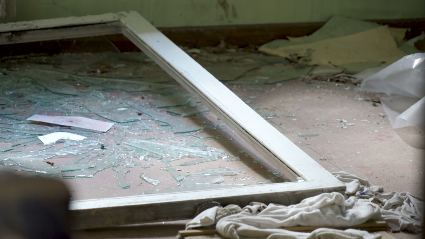 A closer look of the shattered glasses on the floor of the abandoned house | Shutterstock HD Video #1060813942
