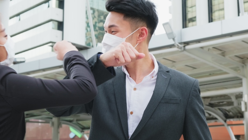 Asian business people wearing protective face mask outside in city due to covid pandemic crisis. Male and female office workers making elbow touch instead of handshake to avoid coronavirus infection. Royalty-Free Stock Footage #1060814638