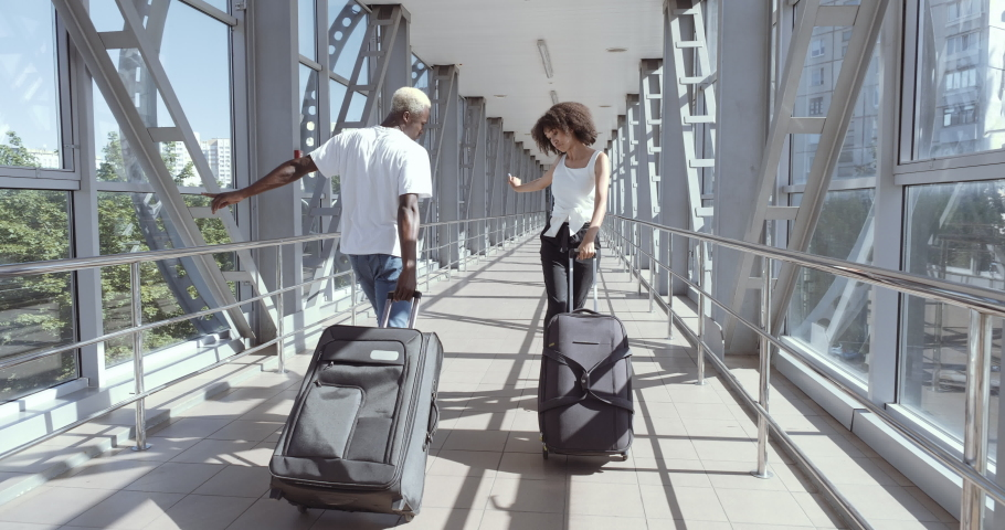 Couple of afro american two teenage lovers go to airport terminal, carry suitcases with luggage, dance with baggage, enjoy travel. Mixed race brother and sister move joyfully, celebrate homecoming