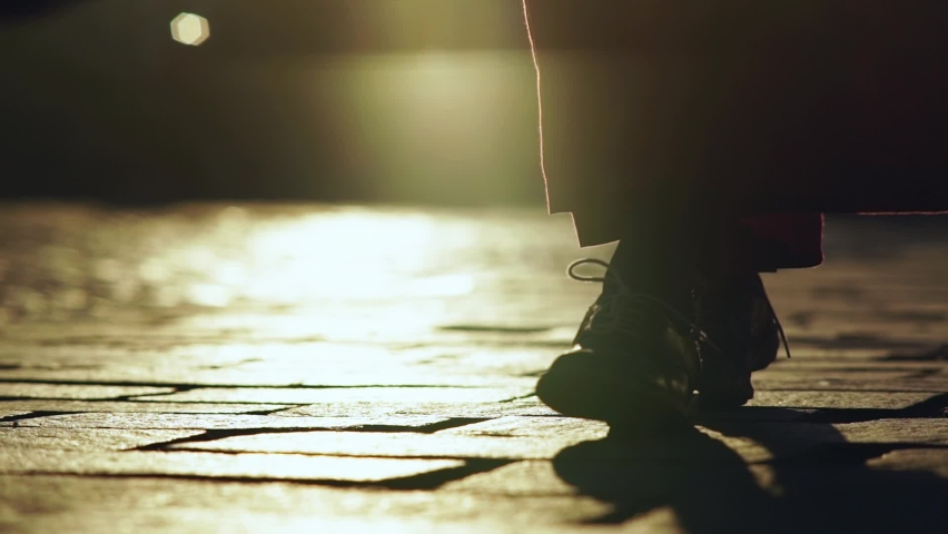silhouette of woman wearing long skirt and flat shoes with laces walking along paved city street at bright sunset light close low angle shot slow motion Royalty-Free Stock Footage #1060819978