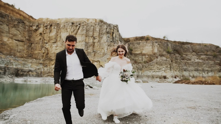 Wedding love story of an elegant couple on the coast of an abandoned canyon with turquoise water Royalty-Free Stock Footage #1060823443