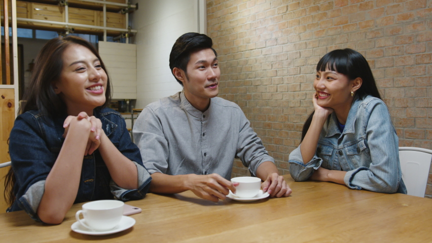 Group of happy young Asia friends having fun a great time and greeting with friendship fist pump while sitting together at cafe restaurant. Coffee shop holiday activity, friendship lifestyle concept.