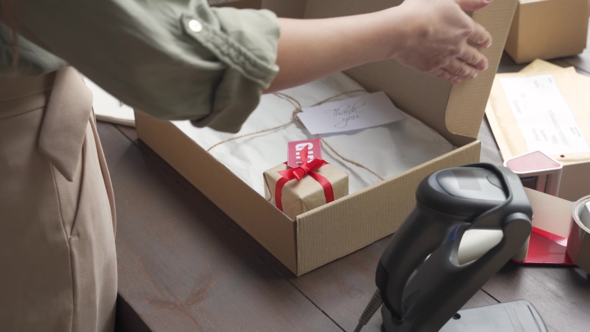 Female online store small business owner worker packing package post shipping ecommerce retail order gift in box preparing forwarding delivery parcel on table. Drop ship service concept, close up view Royalty-Free Stock Footage #1060826347
