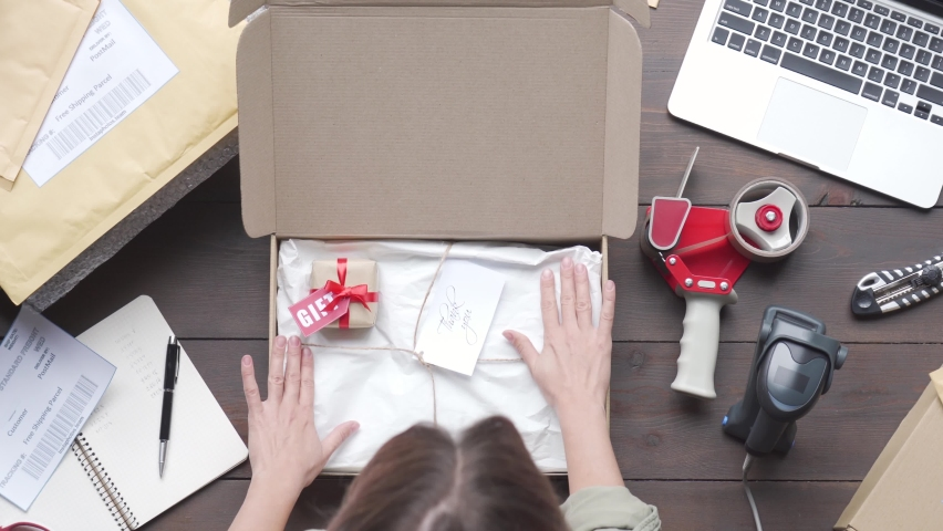 Top above view of female online store small business owner worker packing package post shipping ecommerce retail order gift in box preparing delivery parcel on table. Dropshipping shipment service. Royalty-Free Stock Footage #1060826350