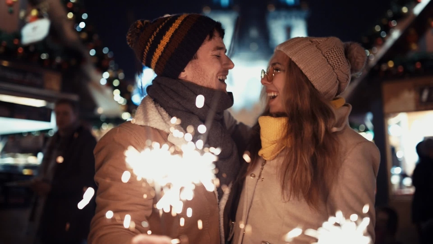 Сouple of lovers with sparklers kissing under the Christmas tree on new year's day to the chimes in the middle of the street in the lights of the Christmas market on the background of the Tree. New
