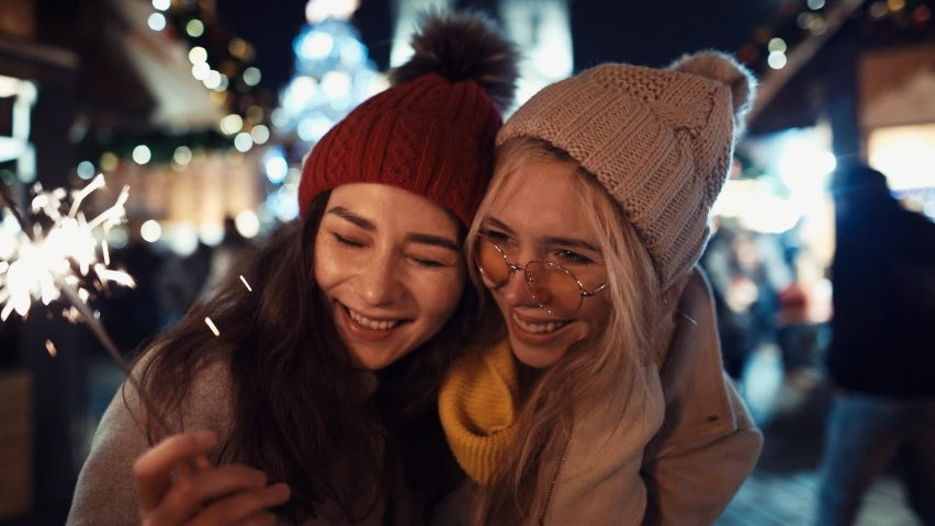 Two Young woman girlfriends kissing and laughing with sparklers in the street on christmas. New year holiday | Shutterstock HD Video #1060826698