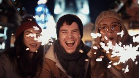 Three happy friends with sparklers call their relatives via video link on new year's eve to the sound of chimes in the middle of the street in the lights of the Christmas market against the background