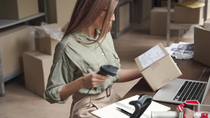 Young female seller or online store worker holding parcel box checking ecommerce post shipping online retail e commerce store order fulfillment using laptop in dropshipping delivery service warehouse. Royalty-Free Stock Footage #1060827886
