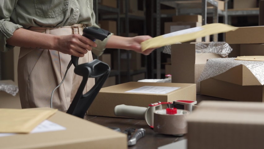 Female seller online store worker holding scanner scanning parcel bar code packing e commerce post shipping box preparing online retail shop order in dropshipping delivery service warehouse. Royalty-Free Stock Footage #1060827889