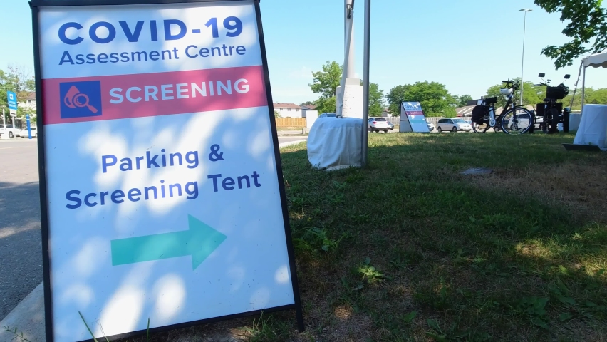 Covid-19 Assessment Centre Screening Parking and Screening Tent sign near hospital in the city. Coronavirus test for workers due pandemic. The fight with virus and second wave control. Royalty-Free Stock Footage #1060829134