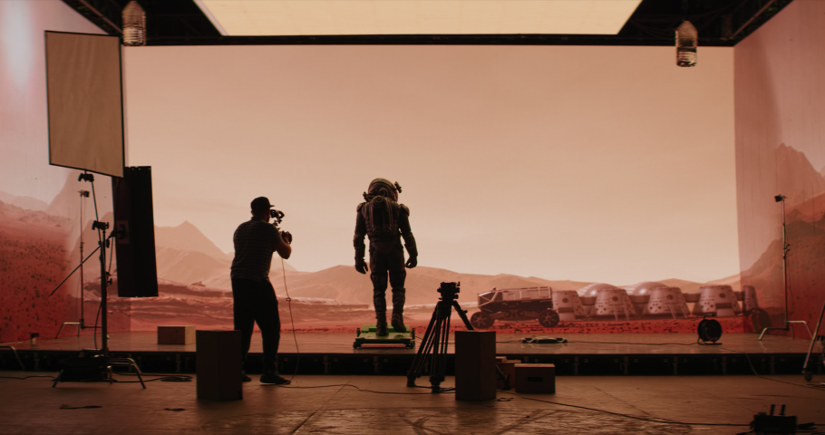 Behind the scenes shot of virtual production stage with huge LED screens, cinematorgapher shooting Mars scene. Future of movie production Royalty-Free Stock Footage #1060829710