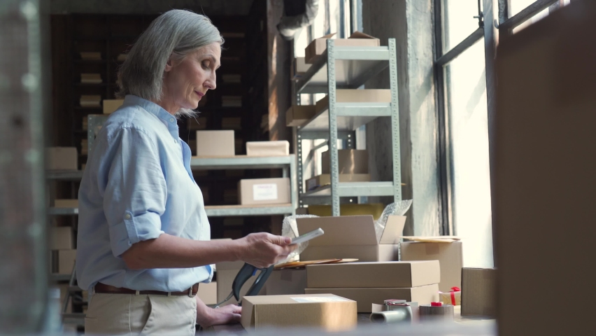 Female mature senior small business owner using mobile app checking parcel box. Warehouse worker, seller holding phone scanning retail dropshipping package postal parcel on cell preparing ship order.