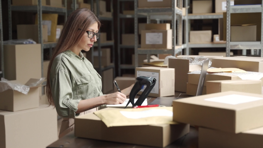 Female warehouse worker online store owner using laptop at work preparing parcel boxes checking ecommerce shipping online retail e commerce store order fulfillment in dropship delivery post office. Royalty-Free Stock Footage #1060830658