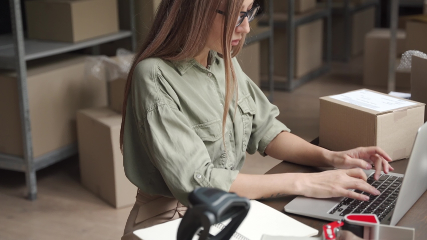 Female entrepreneur online store owner using laptop at work preparing parcel boxes checking ecommerce post shipping online retail e commerce store order fulfillment in dropshipping delivery warehouse. Royalty-Free Stock Footage #1060830661