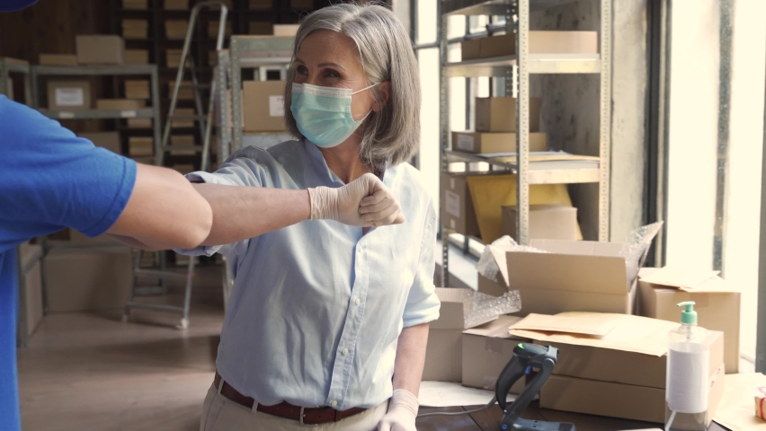 Female warehouse worker manager wearing face mask greeting male courier deliverer giving elbow bump taking shipping parcels boxes for delivery. Covid 19 healthcare protection social distance at work. Royalty-Free Stock Footage #1060832182