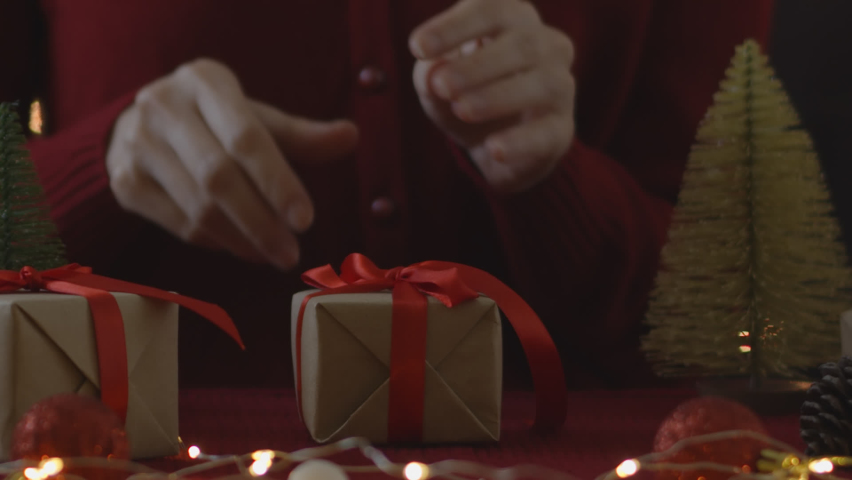 Woman hand untie ribbon at gift box on table for christmas and new year concept. | Shutterstock HD Video #1060835677