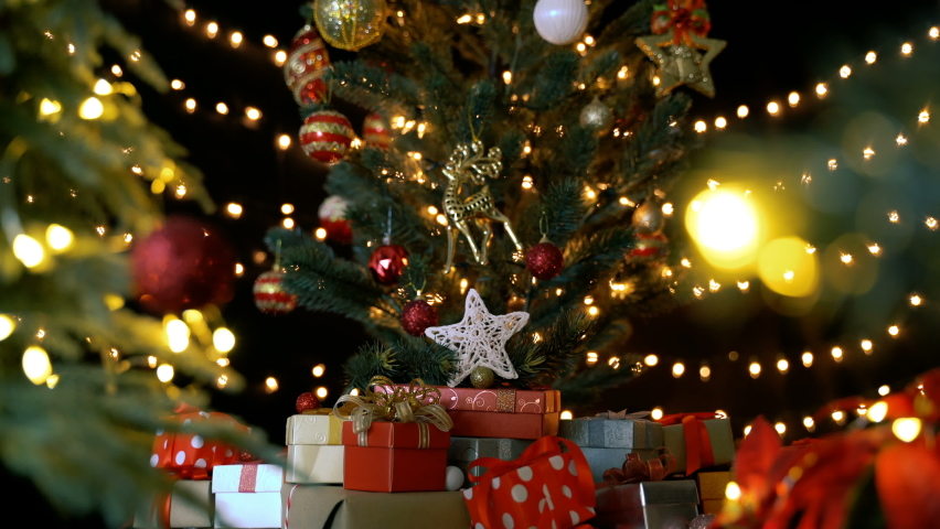 Many gift boxes and christmas decorations under a beautiful decorated christmas tree with bokeh lights in living room at night.