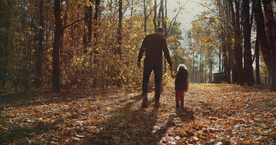 Father and children walking in the park and enjoying the beautiful autumn nature. Happy family on autumn walk. Slow motion | Shutterstock HD Video #1060838968