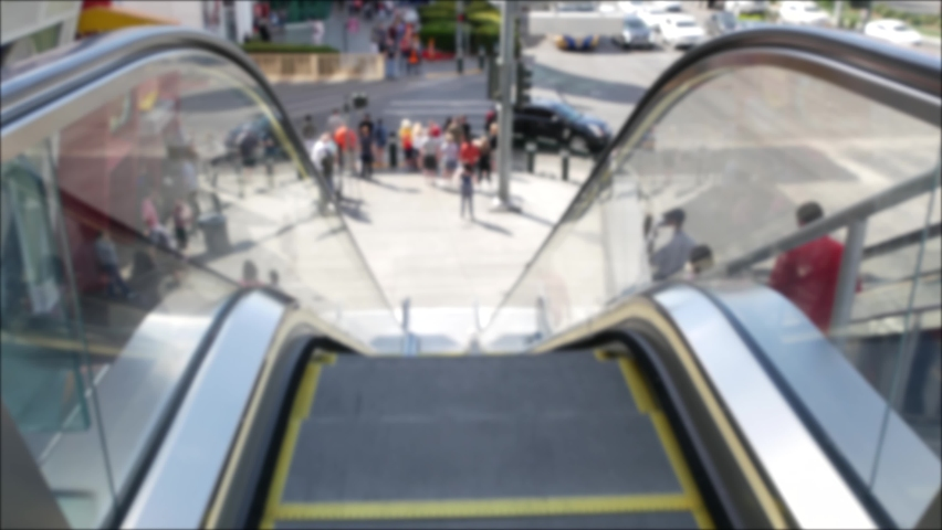 Perspective view thru escalator, defocused unrecognizable group of people on road intersection crosswalk on Strip of Las Vegas, USA. Anonymous blurred pedestrians on walkway in crowded urban downtown. | Shutterstock HD Video #1060839805