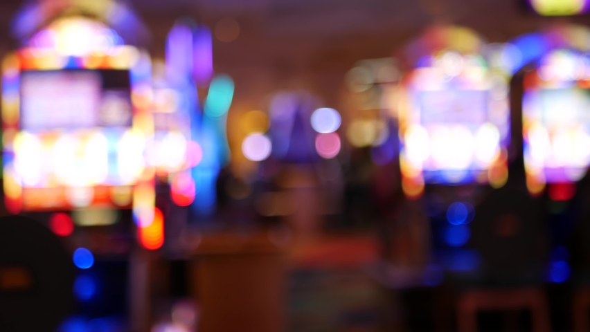 Defocused slot machines glow in casino on fabulous Las Vegas Strip, USA. Blurred gambling jackpot slots in hotel near Fremont street. Illuminated neon fruit machine for risk money playing and betting. | Shutterstock HD Video #1060844437