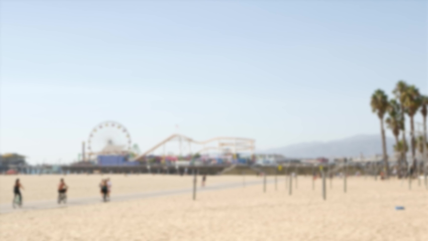 California beach aesthetic, people ride cycles on a bicycle path. Blurred, defocused background. Amusement park on pier and palms in Santa Monica american pacific ocean resort, Los Angeles CA USA. | Shutterstock HD Video #1060844461