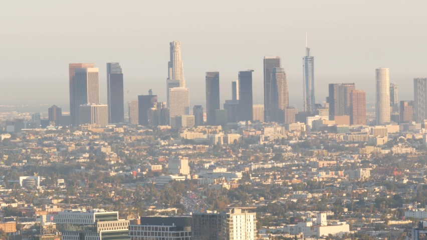 Highrise skyscrapers of metropolis in smog, Los Angeles, California USA. Air toxic pollution and misty urban downtown skyline. Cityscape in dirty fog. Low visibility in city with ecology problems. | Shutterstock HD Video #1060844485