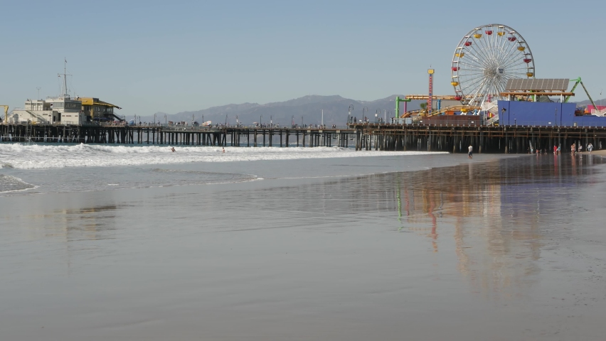 Ocean waves and sandy california beach, classic ferris wheel in amusement park on pier in Santa Monica pacific ocean resort. Summertime iconic view, symbol of Los Angeles, CA USA. Travel concept. | Shutterstock HD Video #1060844545