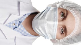 Close-up of woman doctor in surgical mask is looking at camera. Operation, medical practitioner, surgery, transplant, healthcare, medicine, COVID-19 concept. Vertical close-up video
