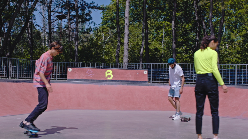 Stylish guys and ladies in a urban skate park have a ride on their skateboard they enjoy the time together in a sunny day | Shutterstock HD Video #1060856302