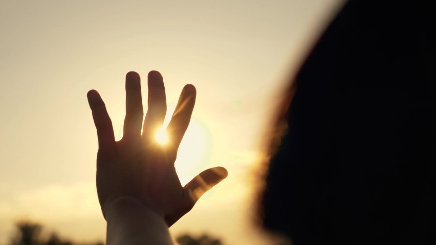 Hand of happy girl at sunset. Sunset between the hands of girl. Happy girl with long hair dreamily stretches out her hand to the sun. Child's dream hand to the sun. happy family concept Royalty-Free Stock Footage #1060857106