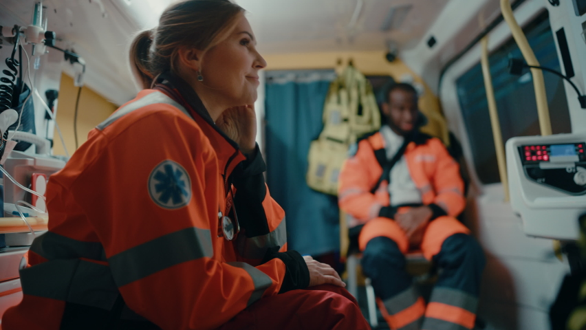 Calm and Happy Female EMS Professional Paramedic Mentally Prepares in Ambulance Vehicle on the Way to a Call. Emergency Medical Technicians are on Their Way to a Call Outside the Healthcare Hospital. Royalty-Free Stock Footage #1060859386