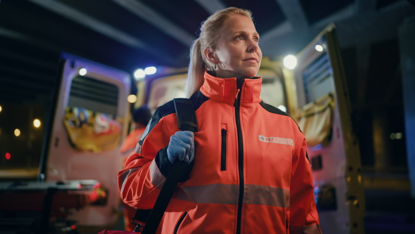"""Portrait of a Female EMS Paramedic Proudly Standing in Front of Camera in High Visibility Medical Orange Uniform with """"Paramedic"""" Text Logo. Successful Emergency Medical Technician or Doctor at Work. Royalty-Free Stock Footage #1060859446"""