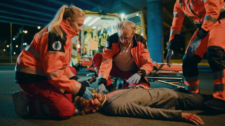 Team of EMS Paramedics Bring a Stretcher from Ambulance Vehicle and Help an Injured Young Person. Emergency Care Assistants Arrived on the Scene of a Traffic Accident on a Street at Night. Royalty-Free Stock Footage #1060859461