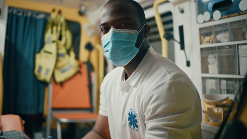 Calm Black African American EMS Professional Paramedic Looks at Camera While Wearing a Safety Face Mask in Ambulance Vehicle. Successful Emergency Medical Technician Outside the Healthcare Hospital. Royalty-Free Stock Footage #1060859497