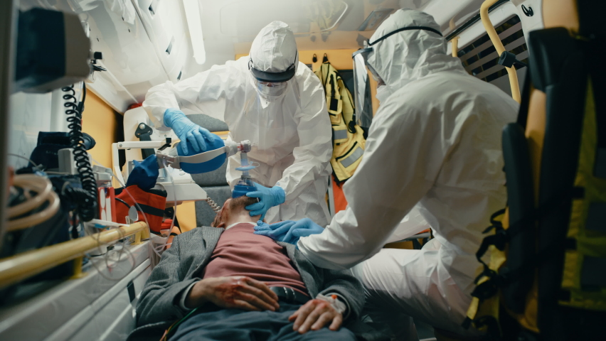 Team of EMS Paramedics in Disposable Coverall Suits Provide Medical Help to Injured Patient on the Way to Hospital. Emergency Care Assistants Putting On Non-Invasive Ventilation Mask in an Ambulance.