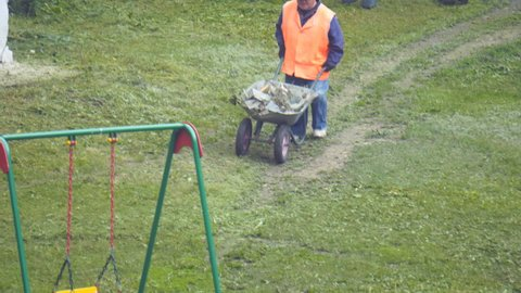 A man with a wheelbarrow with garbage is walking on the grass and the path