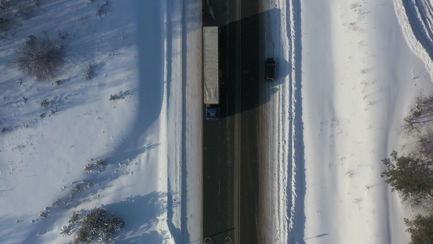 AERIAL. Top view to the truck driving on the snow road in winter time. Delivery concept Royalty-Free Stock Footage #1060865740