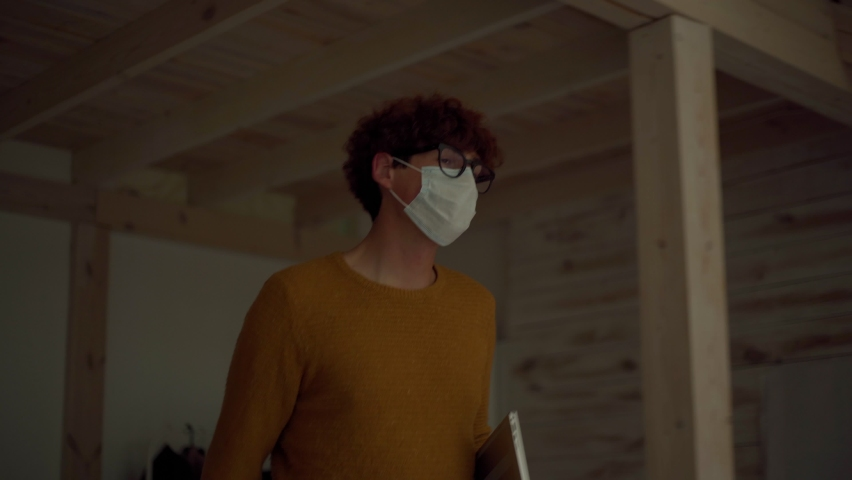 Young man in protective face mask and eyeglasses entering office and refusing to shake hands with male colleague due to covid-19 pandemic. People keeping social distancing at workplace Royalty-Free Stock Footage #1060866427