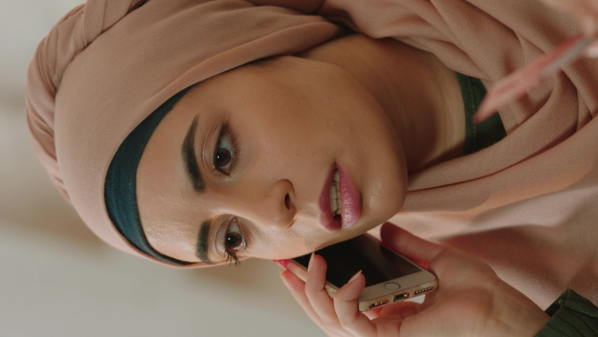 Young muslim woman talking by phone at home with bank customer service.Video for the vertical story. Royalty-Free Stock Footage #1060869082