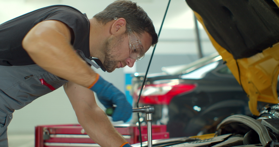 Car mechanic using wrench to repair the engine, car service.